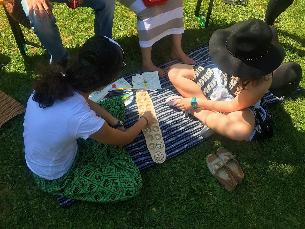 Visitors to the Philippine booth engage in a game of sungka